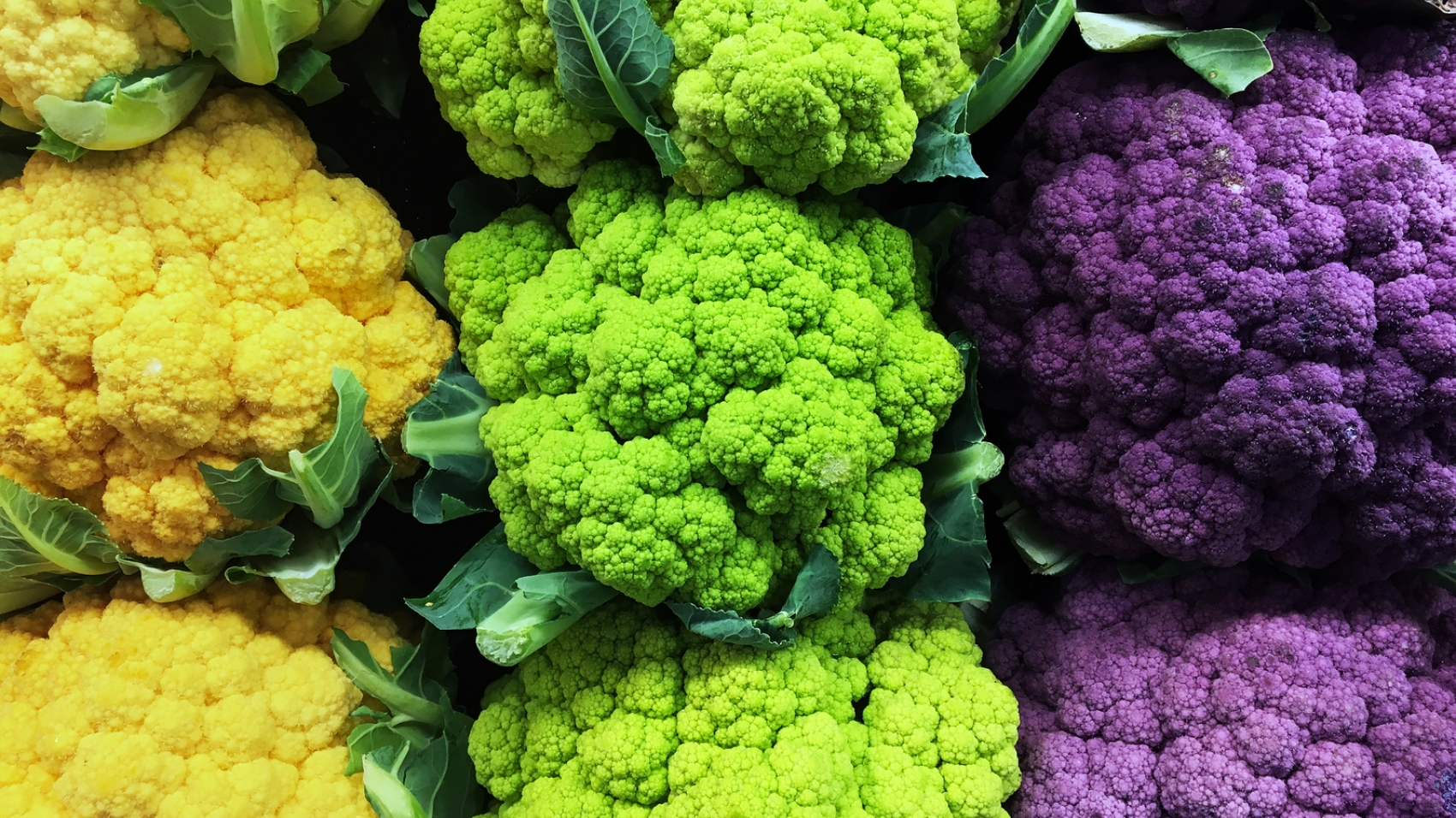 A still-life of yellow, green, and purple cauliflower.